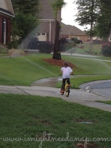 Cooter riding his bicycle through the sprinklers this evening